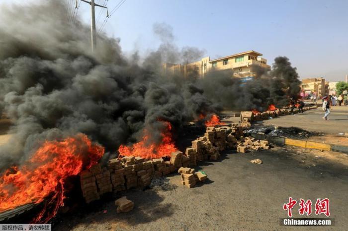 """当地时间10月25日,苏丹局势发生突变,过渡政府总理被""""绑架"""",政府部长被军方抓捕,国家进入紧急状态,大量民众走上街头对军方行动进行抗议,已有7人在抗议活动中死亡,140人受伤。图为抗议活动中燃烧的轮胎。"""