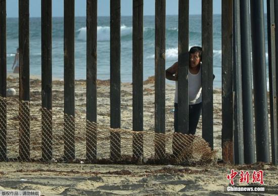 8月20日,圣地亚哥,一道划分美墨边界的栅栏旁,一名男子站在墨西哥这边眺望美国。