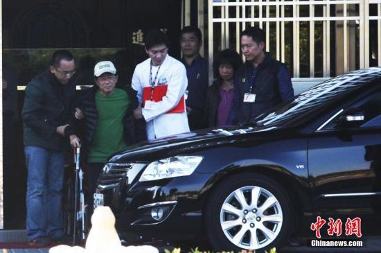 资料图:2015年1月5日,台湾当局前领导人陈水扁获准保外就医。陈水扁坐着轮椅,其子陈致中将其推至台中监狱大门口,并搀扶他上车。 中新社发 路梅 摄