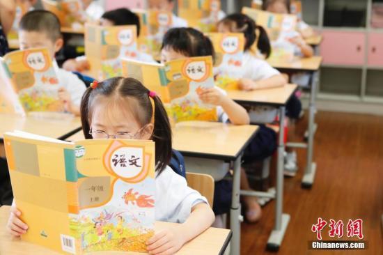 资料图:孩子们在认真阅读《语文》教材。 殷立勤 摄