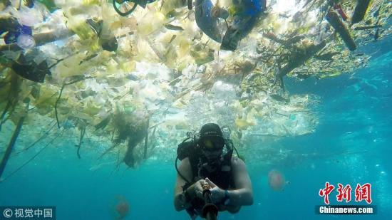 资料图:当地时间2018年3月3日,一名英国男子在巴厘岛海疆潜水时拍下惊心动魄的一幕。大陆中漂浮着大批塑料渣滓:瓶子、袋子、杯子、桶、吸管等等,鱼类及其余大陆生物都避之而不及。 图片起源:视觉中国