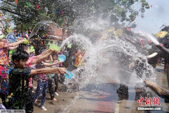 材料图:泰国大象用鼻子向加入泼水节庆典的人群喷水。