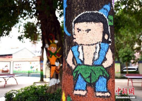 材料图:树木被画上了葫芦娃中的水娃图案。 邓璐 摄