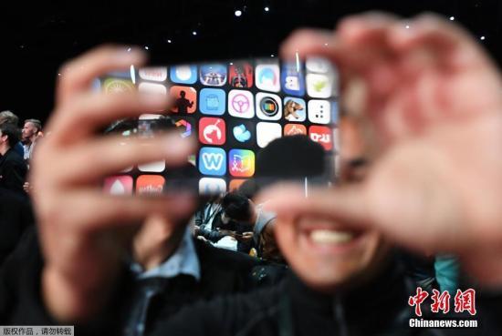 当地时间6月5日凌晨,苹果全球开发者大会在美国加利福尼亚州圣何塞市举行,一名游客用苹果手机记录现场画面。