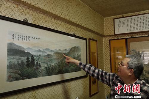 3月,廖德良为记者介绍《寿山清远》图。这是他2005年请画家朋友按实景照片绘制的福州寿山村一带的风貌。中新社记者 毕永光 摄