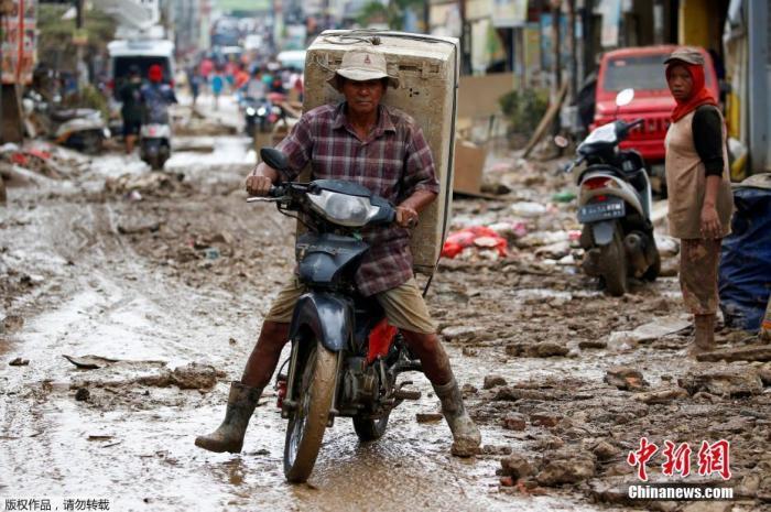 当地时间1月3日,印度尼西亚西爪哇省Bekasi街头一片泥泞。图为当地居民用摩托车运走洗衣机。
