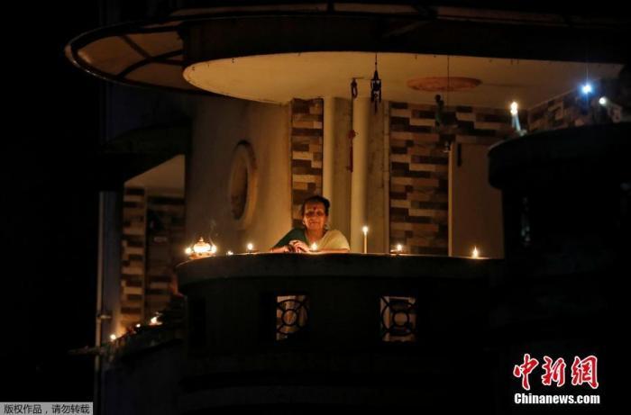 当地时间4月5日21点,印度民众熄灯9分钟,点燃蜡烛和油灯为抗疫祈福。图为印度艾哈迈达巴德一名妇女点燃蜡烛站在阳台上。