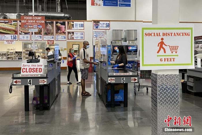 当地时间4月18日,美国休斯敦民众在当地一大型批发超市结账。收银处安装了透明挡板。超市内贴有许多呼吁人们保持6英尺社交距离的提示牌。<a target='_blank' href='http://www.chinanews.com/'>中新社</a>记者 曾静宁 摄