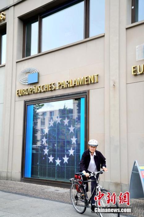 资料图:一名行人骑车经过位于柏林市中心的欧盟委员会驻德国代表处。玻璃墙后有欧盟标志。中新社记者 彭大伟 摄