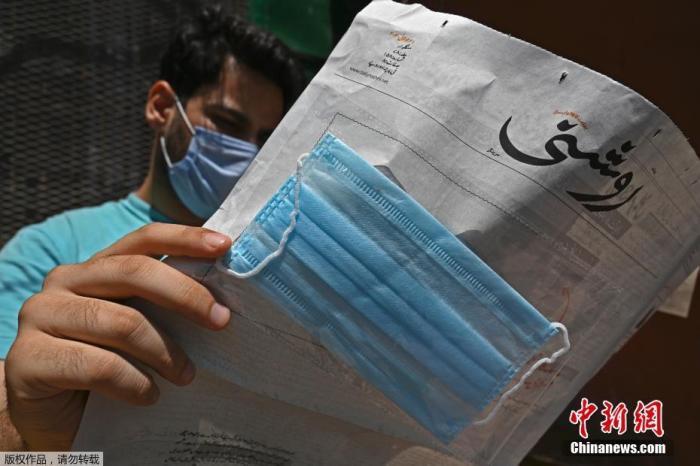 """资料图:当地时间2020年7月23日,印控克什米尔斯利那加,一份当地乌尔都语报纸""""Roshni""""为了提高人们对新冠肺炎的认识,向读者免费提供了口罩,并将其贴在头版。"""