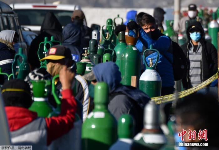 当地时间7月23日,秘鲁第二大城市阿雷基帕,新冠肺炎患者的家属排队给医用氧气瓶充电。