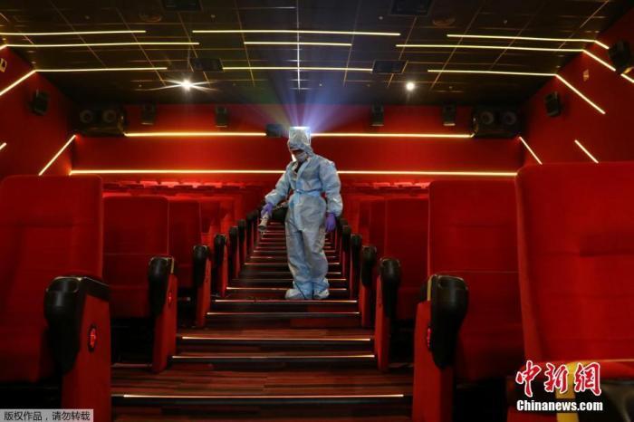 资料图:当地时间2020年10月13日,印度孟买,一名穿着个人防护设备的工人在Inox Leisure电影院重新开放前为座椅消毒。