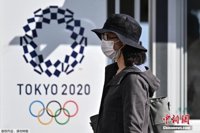 资料图:一名女士走过2020年东京奥运会海报。