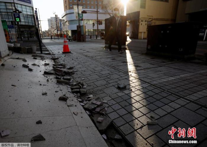 当地时间2月14日,日本福岛县磐城市,一座建筑物的外墙因强烈地震而倒塌,碎片散落一地。