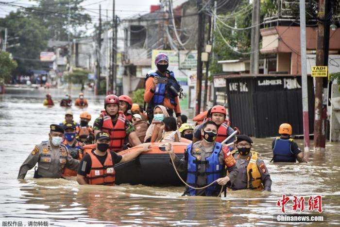 当地时间2月19日,印度尼西亚雅加达一个受洪水影响的社区中,救援人员划船帮助民众撤离。