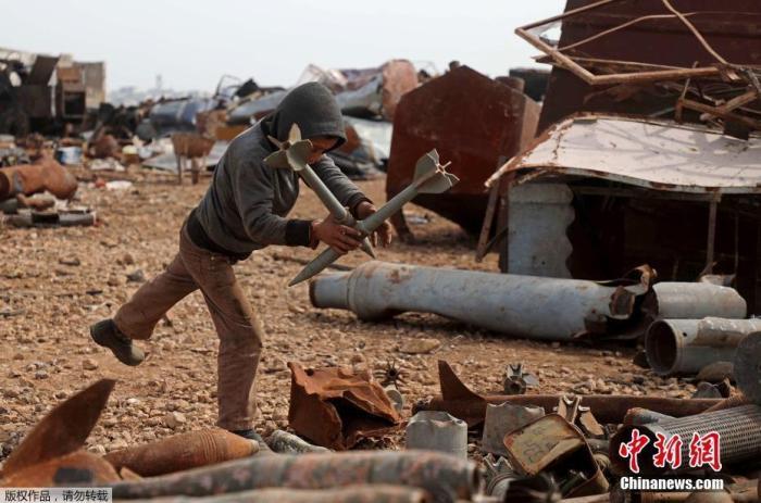 内地时间3月10日,叙利亚伊德利卜省西北部马雷特米斯林镇郊区的一个金属废物场上,人们正在整理堆放的废物。据悉,一个叙利亚家庭4年前从哈马北部农村的Latamneh村搬家到这里后,通过收集和出售包罗未爆弹药壳和废弹药壳在内的金属废物得到收入。图为一个男孩在整理废物。