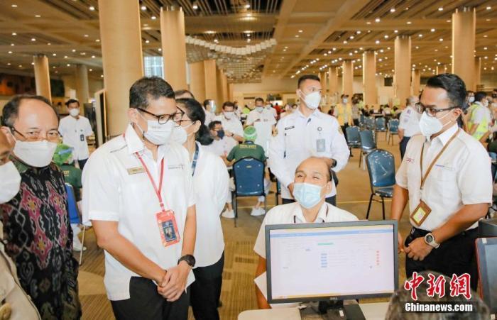 3月22日,印尼旅游和创意经济部长桑迪亚加(左二)视察巴厘岛伍拉莱国际机场员工接种疫苗现场。中新社发 叶露 摄