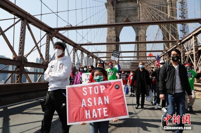 """当地时间4月4日,纽约举行反仇恨亚裔大游行,上万民众手持标语在曼哈顿弗利广场集会后,游行穿过布鲁克林大桥至布鲁克林卡德曼广场。图为游行队伍中手持""""停止仇恨亚裔""""标语的亚裔孩童。 a target='_blank' href='https://www.chinanews.com/'/p中新社/a记者 廖攀 摄"""