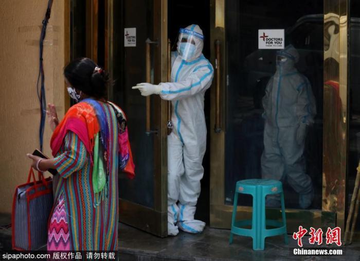 4月27日,印度通报新增逾32万新冠确诊病例,连续第6天超过30万例,累计确诊升至近1800万,死亡人数逼近20万。连续激增的确诊病例,导致印度多地医疗系统瘫痪,许多患者只能在临时搭建的场所接受治疗。图为医护人员在宴会厅改建的临时病房门口。