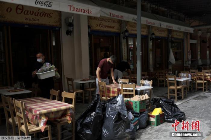 资料图:5月4日消息,希腊餐饮业恢复经营。当地时间5月3日,希腊雅典,一家餐馆的服务生在收拾餐桌。