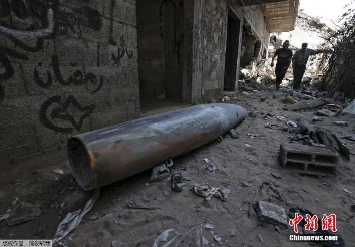 当地时间5月18日,巴以冲突持续,加沙地带一居民区出现一枚未引爆的炸弹。图为炸弹倒卧在一幢房屋门前。