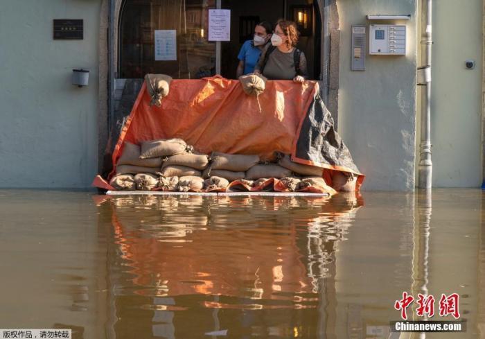 图为当地时间2021年7月18日,在德国帕索,两名女士从一家旅馆的入口处眺望,洪水阻挡了多瑙河的水流。