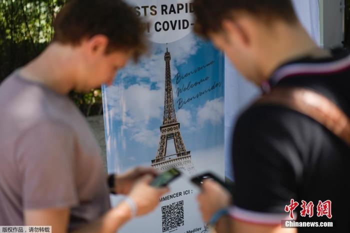 当地时间2021年7月21日,法国巴黎,游客在埃菲尔铁塔入口处进行新冠检测。图为游客在巴黎埃菲尔铁塔登记接受COVID-19测试。