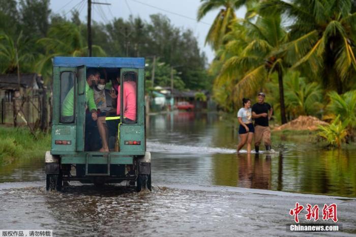 """资料图:当地时间8月28日,飓风""""艾达""""登陆古巴,带来强风降雨天气,古巴阿尔特米萨省Guanimar部分道路被淹。图为汽车在被雨水淹没的街道上行驶。"""