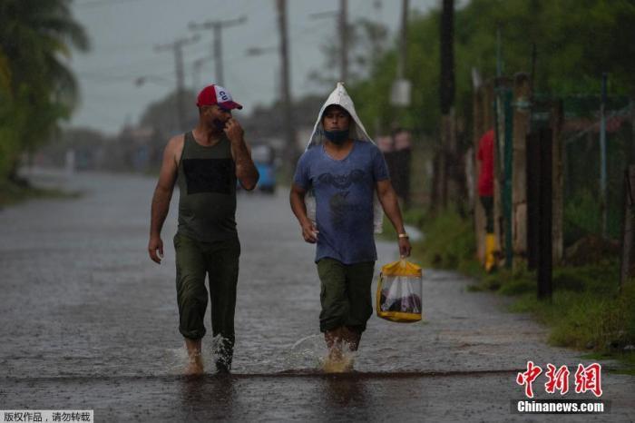 """当地时间8月28日,飓风""""艾达""""登陆古巴,带来强风降雨天气,古巴阿尔特米萨省Guanimar部分道路被淹。图为行人走在被雨水淹没的街道上。"""